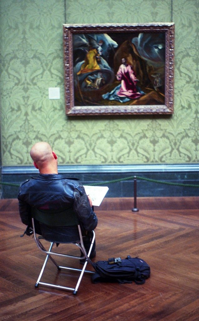 man sitting in front of painting in art gallery