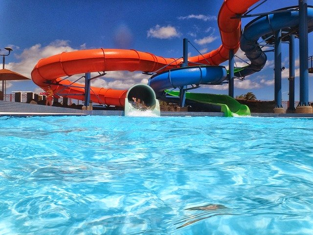 waterpark with aqua blue glistening water and a long blue and red slide